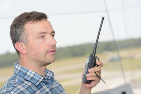 Photo pour Profile of man using walkie talkie - image libre de droit
