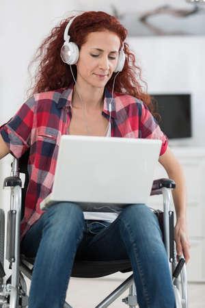 Photo pour happy female in wheelchair listening to music on laptop - image libre de droit