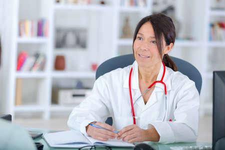 Photo pour beautiful young smiling female doctor sitting at the desk - image libre de droit
