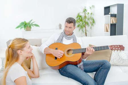Photo pour Man playing guitar to lady - image libre de droit