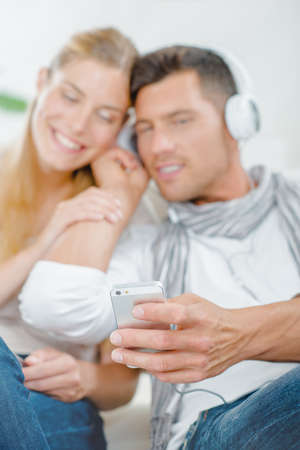 Photo pour Couple with cell phone and headphones - image libre de droit