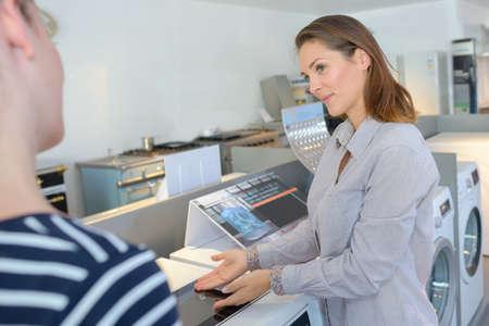 Photo pour Lady demonstrating electrical appliance - image libre de droit
