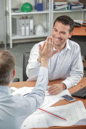 men having a high five inside an office
