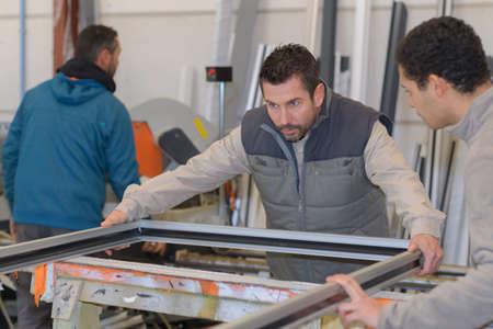 Photo pour men working at plastic door and window factory - image libre de droit