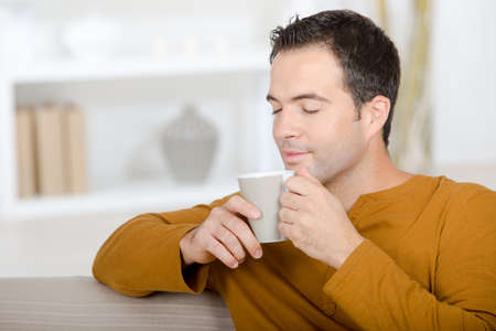 Photo pour relaxing at home on the couch and having a tea - image libre de droit
