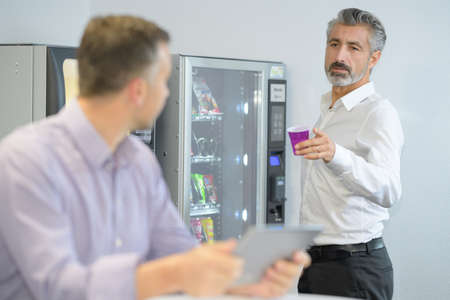 Photo for Businessman offering coffee from vending machine - Royalty Free Image