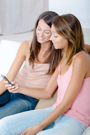 Photo pour Girlfriends looking at cellphone screen and laughing - image libre de droit
