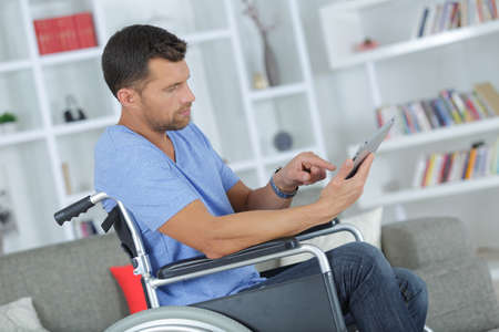 handsome man using a tablet in a wheelchair at home