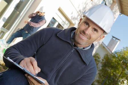 Photo pour happy confident builder writing and using clipboard - image libre de droit