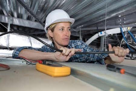 Photo pour Female electrician working in confined space - image libre de droit