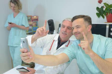 Photo pour smiling team of doctors and nurses at hospital taking selfie - image libre de droit
