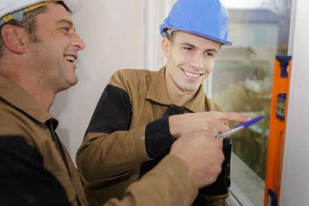 Photo pour smiling repairman measuring with the help of builder level - image libre de droit