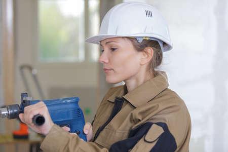 Photo pour woman using electric screwdriver to drill screw into dark wood - image libre de droit