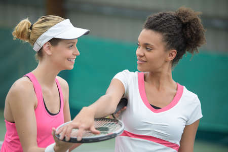 two beautiful female tennis players holding rackets