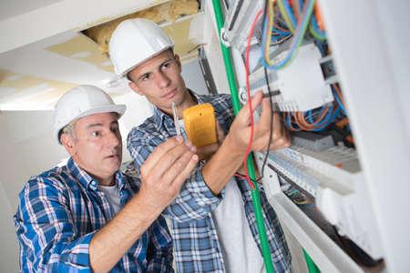 Foto de young apprentice with electrician professional - Imagen libre de derechos
