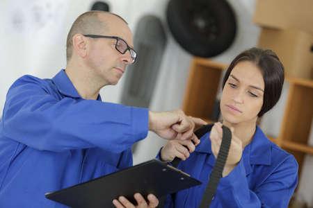 two motor mechanic engineers examining timing belt