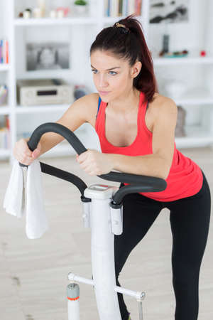 sporty woman exercising on step machine in bright living room