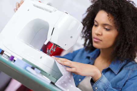 Photo pour woman sewing at her working place in fashion workshop - image libre de droit