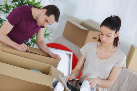 Photo pour young couple unpacking or packing boxes - image libre de droit