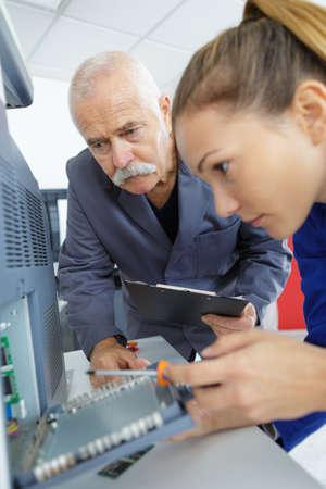 female appprentice repairing a computer hard disk