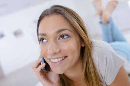 Photo pour smiling woman using a smartphone while relaxing at home - image libre de droit