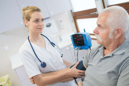 A female doctor checking an old man's arterial blood pressure