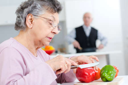 old lady chopping red and green peppers