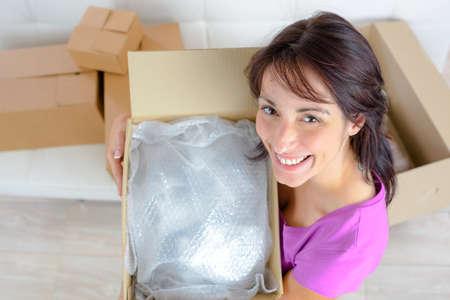 Photo pour smiling young woman opening a carton box - image libre de droit