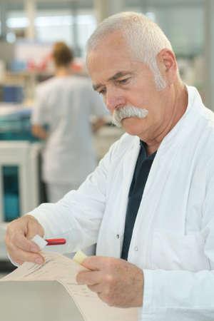 Photo pour positive senior doctor checking a paper - image libre de droit