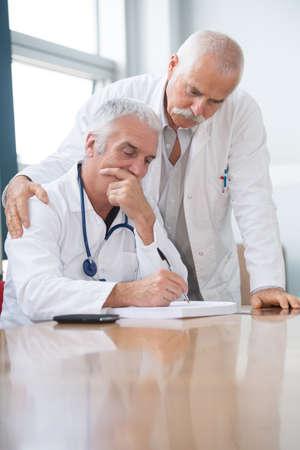 Photo pour friendly doctors checking some documents - image libre de droit