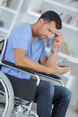 young man using a tablet in a wheelchair
