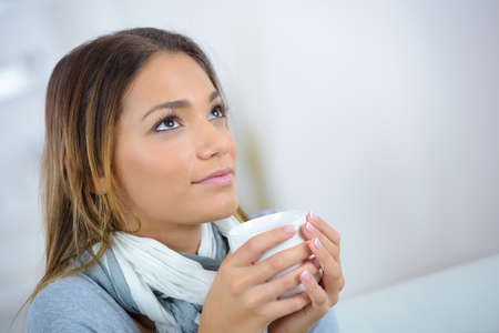 Photo pour young beautiful woman drinking coffee or tea and thinking - image libre de droit