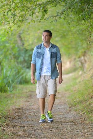 Photo pour happy man walking and relaxing in park - image libre de droit