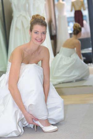Photo pour Portrait of woman trying on wedding shoes - image libre de droit