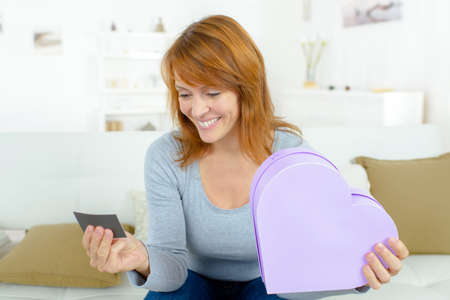 beautiful woman with valentines day gift in heart shaped box