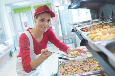 Photo pour buffet female worker servicing food in cafeteria - image libre de droit