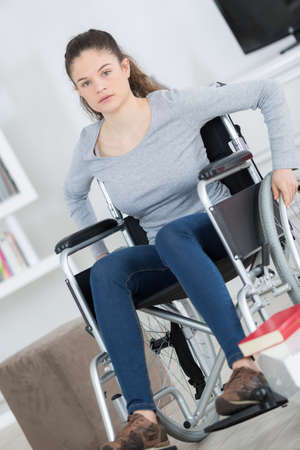 Photo pour young woman in wheelchair looking at camera - image libre de droit