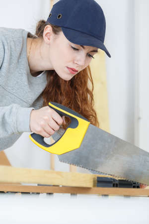 young craftswoman cutting a wooden board with a handsaw