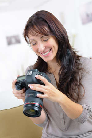 Photo pour smiling female photographer checking picture preview on camera screen - image libre de droit