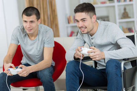 Photo pour happy young brothers playing video games - image libre de droit