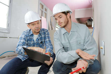 Photo pour building engineers in hard hat thinking and writing on clipboard - image libre de droit