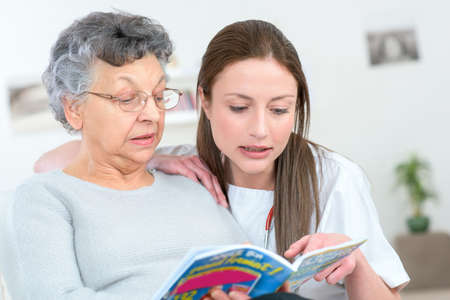 caregiver reading a book with an elderly patient