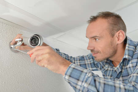 technician adjusting cctv camera on wall