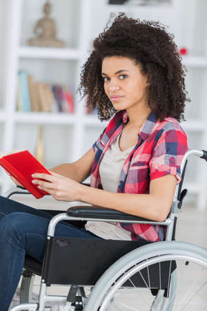 Photo pour young worried woman in wheelchair holding book - image libre de droit
