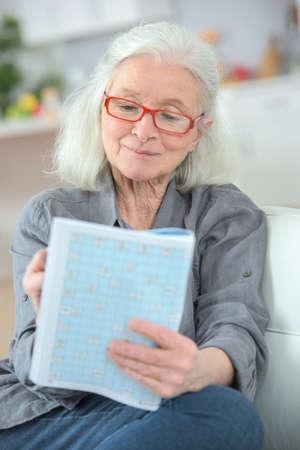 Photo pour elderly woman doing crossword puzzle - image libre de droit