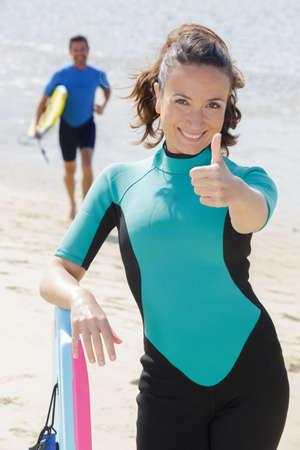 Photo pour successful couple of surfers showing thumbs up - image libre de droit