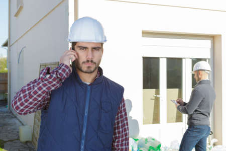 Photo pour supervising a construction using cell phone outdoors - image libre de droit