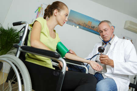 Photo pour doctor takes tanometrom pressure of female patient in wheelchair - image libre de droit