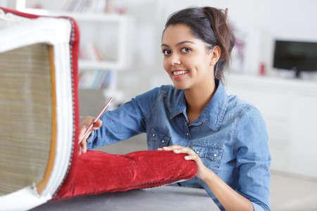 Photo pour woman upholstering chair at home - image libre de droit