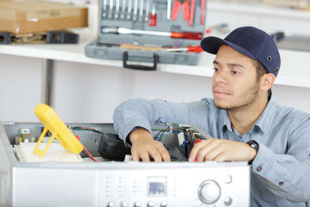 Photo pour happy young male electrician fixing a washer - image libre de droit
